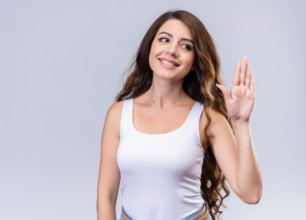 Smiling young beautiful girl gesturing hi  with copy space