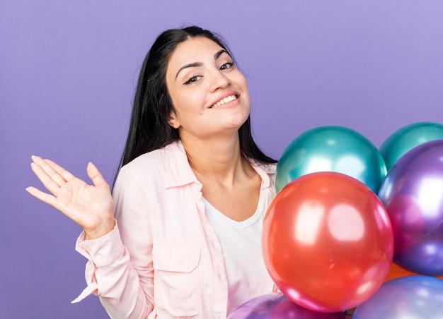 Улыбающаяся молодая красивая девушка держит воздушные шары, протягивая руку, изолированную на синей стене