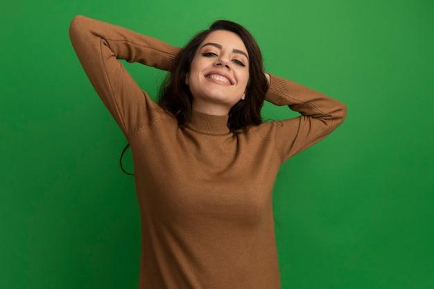 녹색 벽에 고립 된 머리 뒤에 손을 잡고 웃는 젊은 아름 다운 소녀