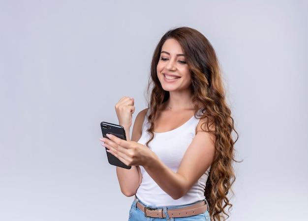 Sorridente giovane bella ragazza che tiene e guardando il telefono cellulare con il pugno alzato con lo spazio della copia