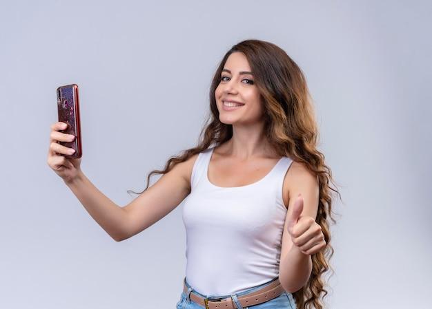 Улыбающаяся молодая красивая девушка держит мобильный телефон и показывает палец вверх