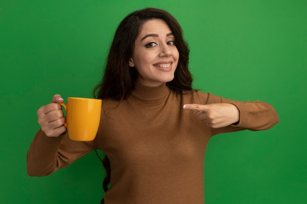 Smiling young beautiful girl holding and points at cup of tea isolated on green wall