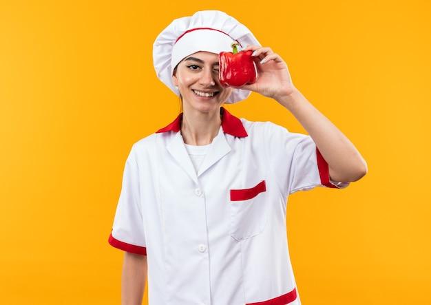 Улыбающаяся молодая красивая девушка в униформе шеф-повара покрыла глаза перцем, изолированным на оранжевой стене