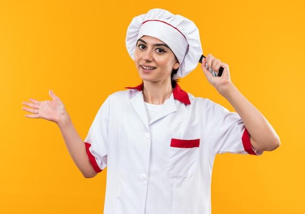 オレンジ色の壁で隔離の頭の後ろにフライパンを保持しているシェフの制服を着た若い美しい少女の笑顔