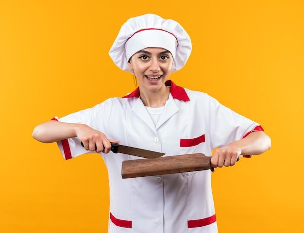 주황색 벽에 분리된 도마와 칼을 들고 요리사 유니폼을 입은 웃고 있는 아름다운 소녀