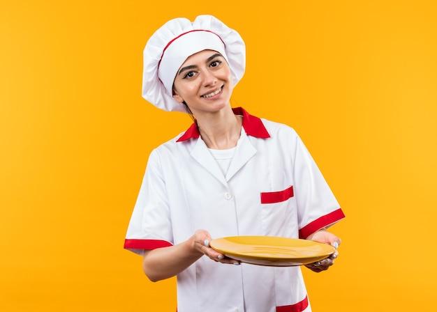Улыбающаяся молодая красивая девушка в униформе шеф-повара, протягивая тарелку перед камерой