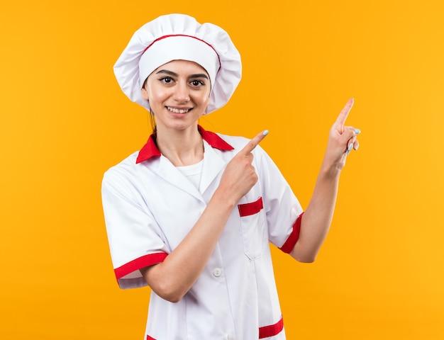 Улыбающаяся молодая красивая девушка в униформе шеф-повара указывает сбоку, изолированную на оранжевой стене с копией пространства