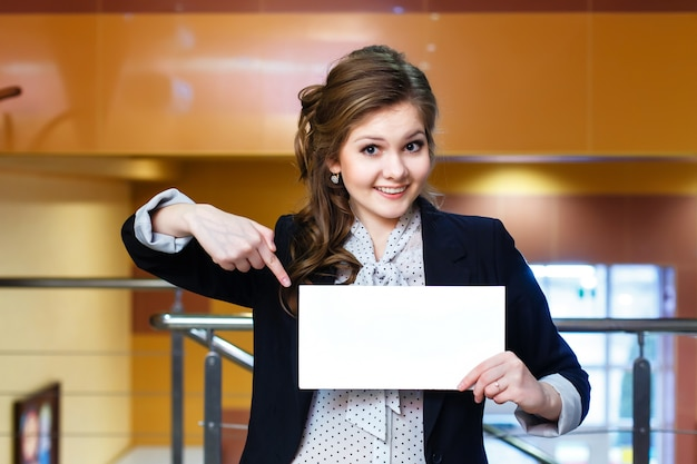 Smiling young beautiful girl shows on blank white card