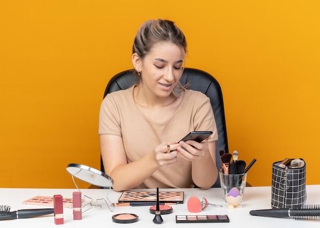 La giovane bella ragazza sorridente si siede al tavolo con gli strumenti per il trucco tenendo il pennello per il trucco e guardando il telefono in mano isolato su sfondo arancione