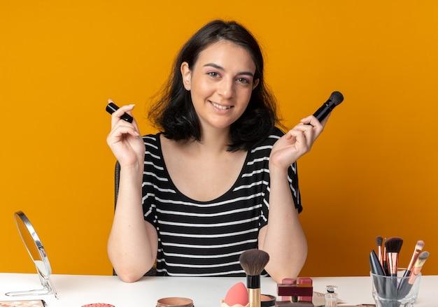 La giovane bella ragazza sorridente si siede alla tavola con gli strumenti di trucco che tengono la spazzola della polvere isolata su fondo arancione