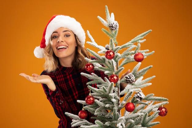 오렌지 배경에 고립 손을 확산 크리스마스 모자를 쓰고 크리스마스 트리 뒤에 서있는 젊은 아름 다운 소녀 미소