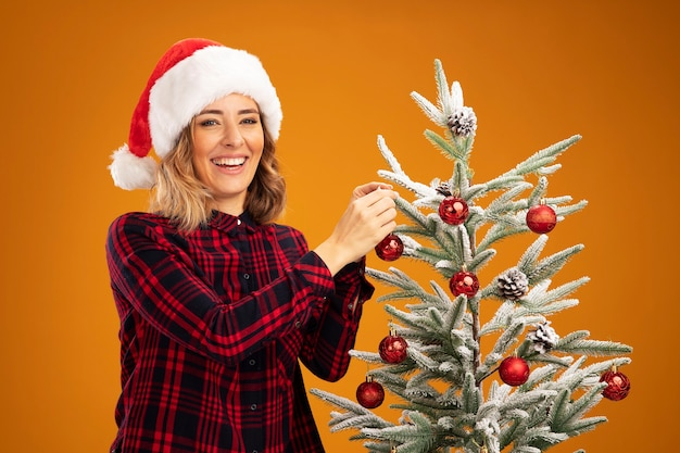 Smiling young beautiful girl standing nearby christmas tree wearing christmas hat decorate christmas tree decorate tree isolated on orange background