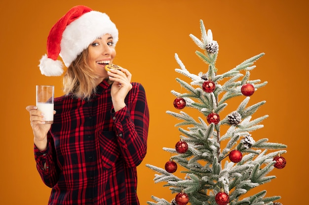 Smiling young beautiful girl standing nearby christmas tree wearing christmas hat holding glass of milk and trying cookies isolated on orange background