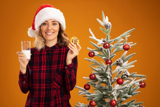 Smiling young beautiful girl standing nearby christmas tree wearing christmas hat holding glass of milk with cookies isolated on orange background