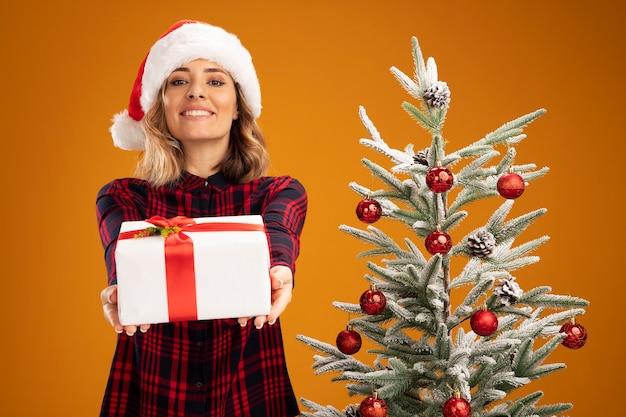 オレンジ色の背景で隔離のカメラでギフトボックスを差し出してクリスマス帽子をかぶってクリスマスツリーの近くに立っている若い美しい少女の笑顔