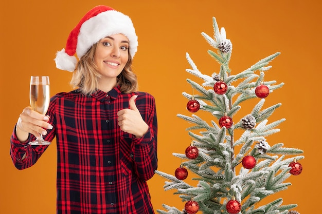 Sorridente giovane bella ragazza in piedi vicino all'albero di natale con il cappello di natale che porge un bicchiere di champagne alla telecamera che mostra il pollice in su isolato su sfondo arancione orange