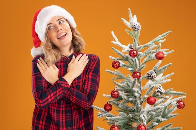 Sorridente giovane bella ragazza in piedi vicino albero di natale che indossa il cappello di natale mettendo le mani sulla spalla isolata su sfondo arancione