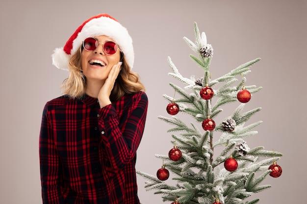 흰색 배경에 고립 된 뺨에 손을 넣어 안경 크리스마스 모자를 쓰고 크리스마스 트리 근처에 서있는 젊은 아름 다운 소녀 미소