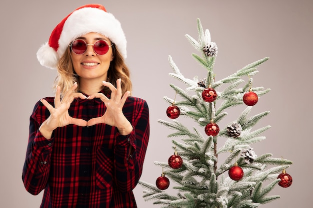 Smiling young beautiful girl standing nearby christmas tree wearing christmas hat with glasses showing heart gesture isolated on white background