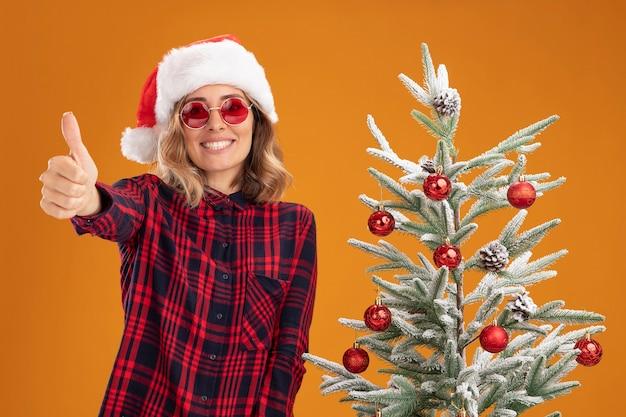 オレンジ色の背景で隔離の親指を示すメガネとクリスマス帽子をかぶってクリスマスツリーの近くに立っている若い美しい少女の笑顔
