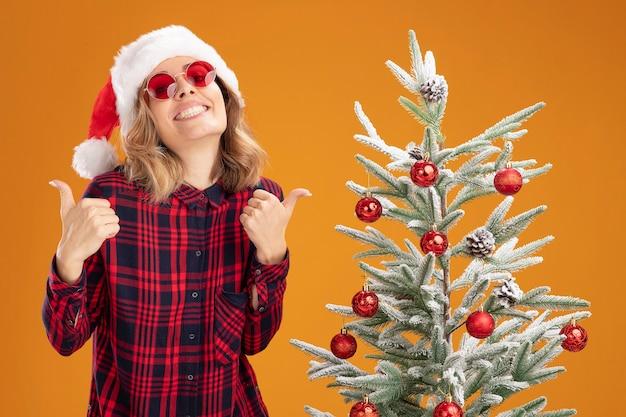 Улыбающаяся молодая красивая девушка, стоящая рядом с елкой в новогодней шапке в очках, показывает жест да, изолированные на оранжевом фоне
