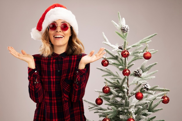 Smiling young beautiful girl standing nearby christmas tree wearing christmas hat with glasses spreading hands isolated on white background