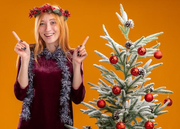 赤いドレスを着て、オレンジ色の壁に孤立した首のポイントに花輪を捧げるクリスマス ツリーの近くに立っている笑顔の美しい少女