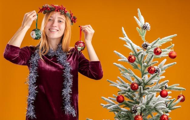 Giovane bella ragazza sorridente che sta vicino all'albero di natale che porta vestito rosso e corona con la ghirlanda sul collo che tiene le palle di natale isolate su fondo arancio