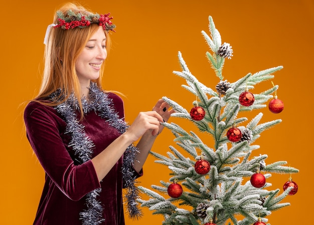 Smiling young beautiful girl standing nearby christmas tree wearing red dress and wreath with garland on neck holding tree isolated on orange wall