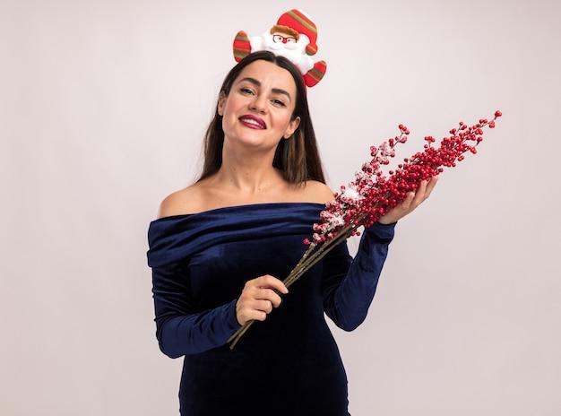 Улыбающаяся молодая красивая девушка в синем платье и рождественском обруче для волос держит ветку рябины на белом фоне