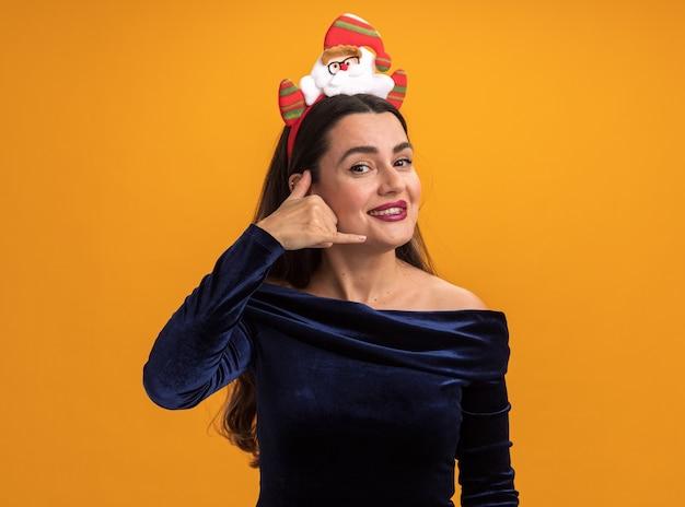 青いドレスとオレンジ色の背景で隔離の電話ジェスチャーを示すおもちゃを保持しているクリスマスヘアフープを身に着けている若い美しい少女