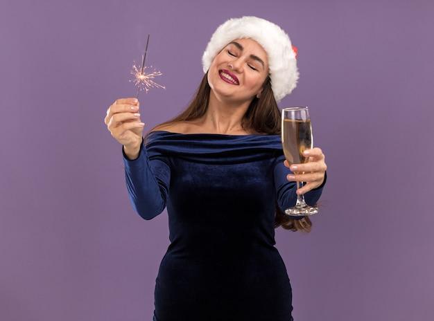 Giovane bella ragazza sorridente che porta vestito blu e cappello di natale che tiene le stelle filanti e che tiene fuori il bicchiere di champagne alla macchina fotografica isolata su fondo viola