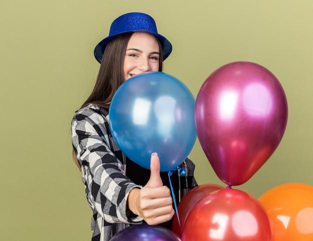 風船の後ろに立っている青い帽子をかぶって笑顔の若い美しい少女は、オリーブグリーンの壁に分離された親指を示しています