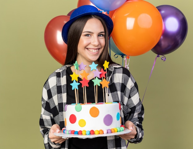 Smiling young beautiful girl wearing blue hat standing in front balloons holding cake isolated on olive green wall
