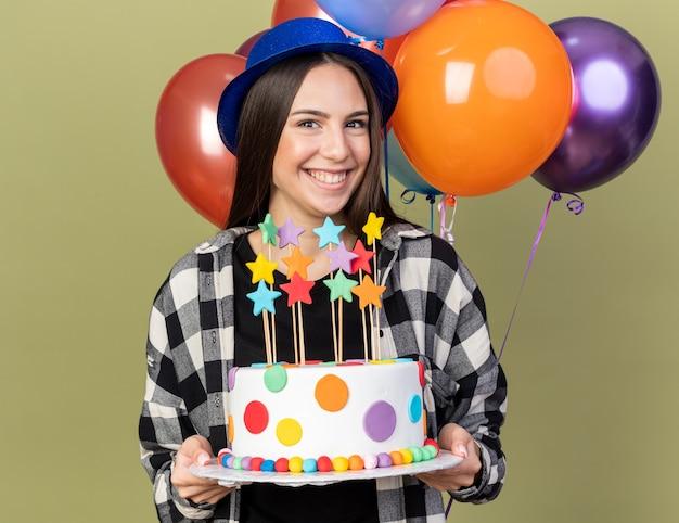 オリーブグリーンの壁に分離されたケーキを保持している前の風船に立っている青い帽子をかぶって笑顔の若い美しい少女