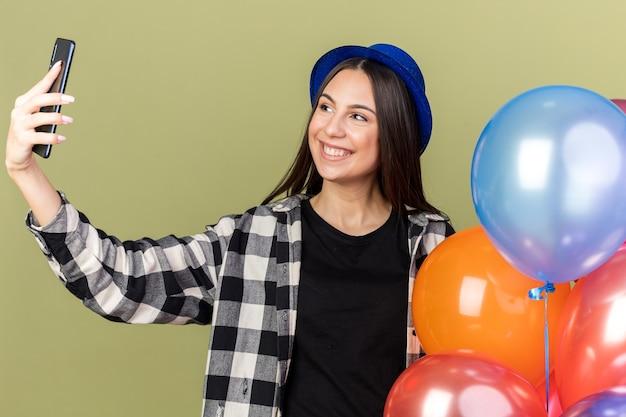 風船の近くに立っている青い帽子をかぶって、自分撮りをする笑顔の若い美しい少女