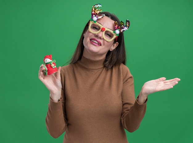 Smiling young beautiful girl wearing brown sweater and christmas glasses holding christmas toy spreading hand isolated on green wall