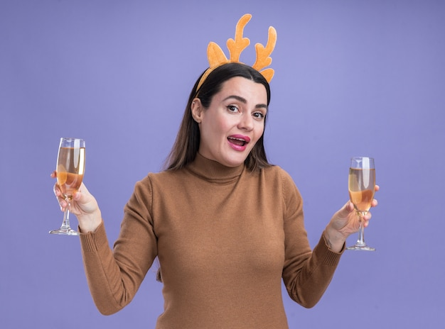 Smiling young beautiful girl wearing brown sweater with christmas hair hoop holding two glass of champagne isolated on blue wall
