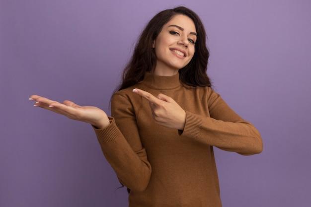 Sorridente giovane bella ragazza che indossa un maglione a collo alto marrone che finge di tenere e indica qualcosa di isolato sul muro viola