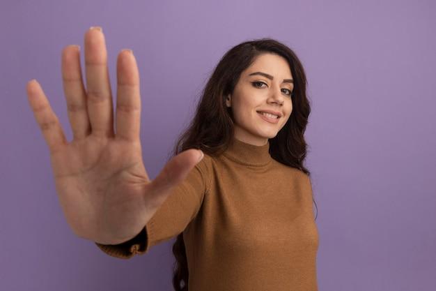 Sorridente giovane bella ragazza che indossa un maglione a collo alto marrone che mostra cinque isolati sulla parete viola