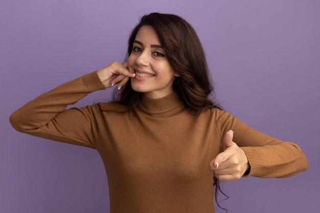 보라색 벽에 고립 된 전화 제스처와 포인트를 보여주는 갈색 터틀넥 스웨터를 입고 웃는 젊은 아름 다운 소녀