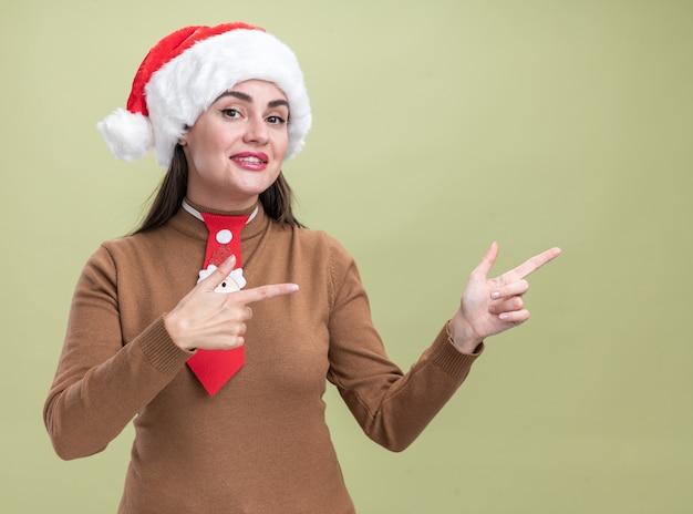 복사 공간 올리브 녹색 벽에 고립 된 측면에서 크리스마스 모자와 넥타이 포인트를 입고 웃는 젊은 아름 다운 소녀