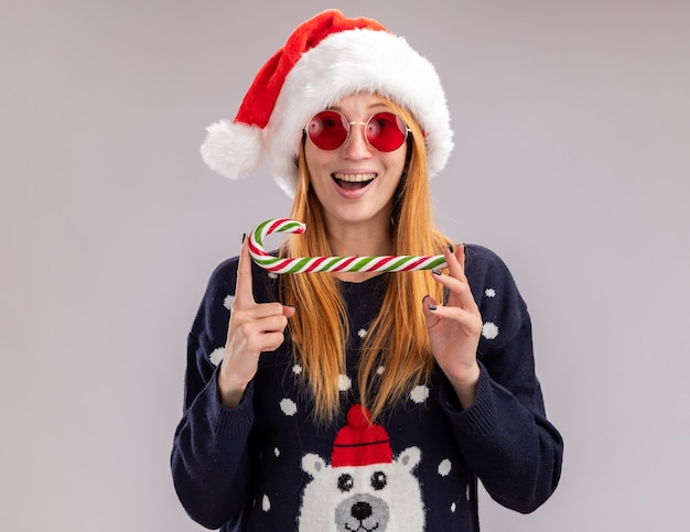 Smiling young beautiful girl wearing christmas hat and glasses holding christmas candy isolated on white wall