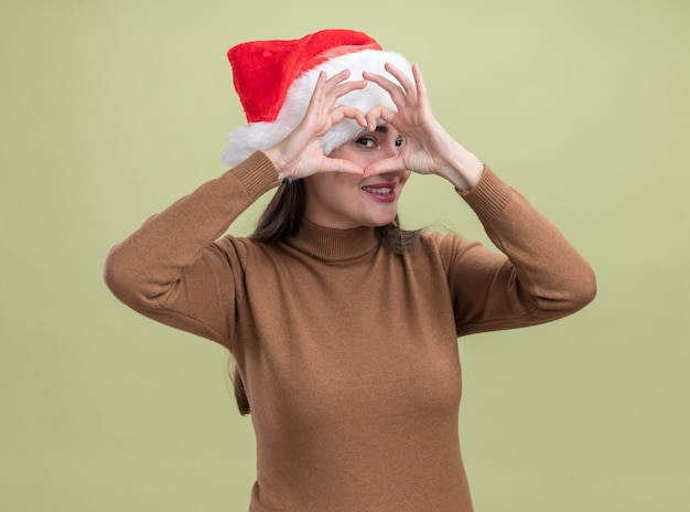 Smiling young beautiful girl wearing christmas hat showing heart gesture isolated on olive green background