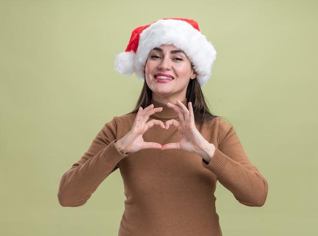 Улыбающаяся молодая красивая девушка в новогодней шапке показывает жест сердца на оливково-зеленом фоне