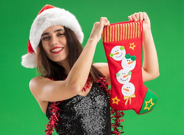 Smiling young beautiful girl wearing christmas hat with garland on neck holding christmas sock isolated on green background
