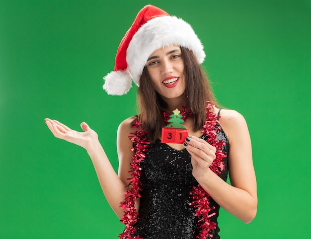 Smiling young beautiful girl wearing christmas hat with garland on neck holding christmas toy spreading hand isolated on green wall