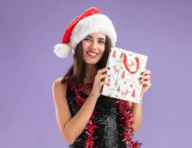 Sorridente giovane bella ragazza che indossa il cappello di natale con la ghirlanda sul collo che tiene il sacchetto regalo isolato su sfondo viola