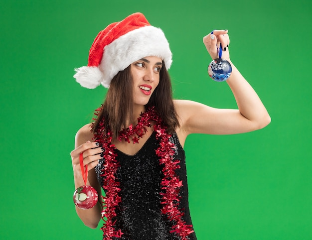 Smiling young beautiful girl wearing christmas hat with garland on neck holding and looking at christmas tree balls isolated on green background
