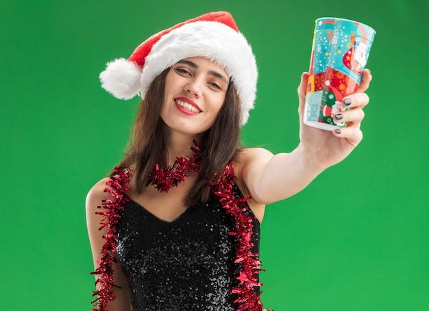 Giovane bella ragazza sorridente che porta il cappello di natale con la ghirlanda sul collo che tiene fuori la tazza di natale alla macchina fotografica isolata su fondo verde